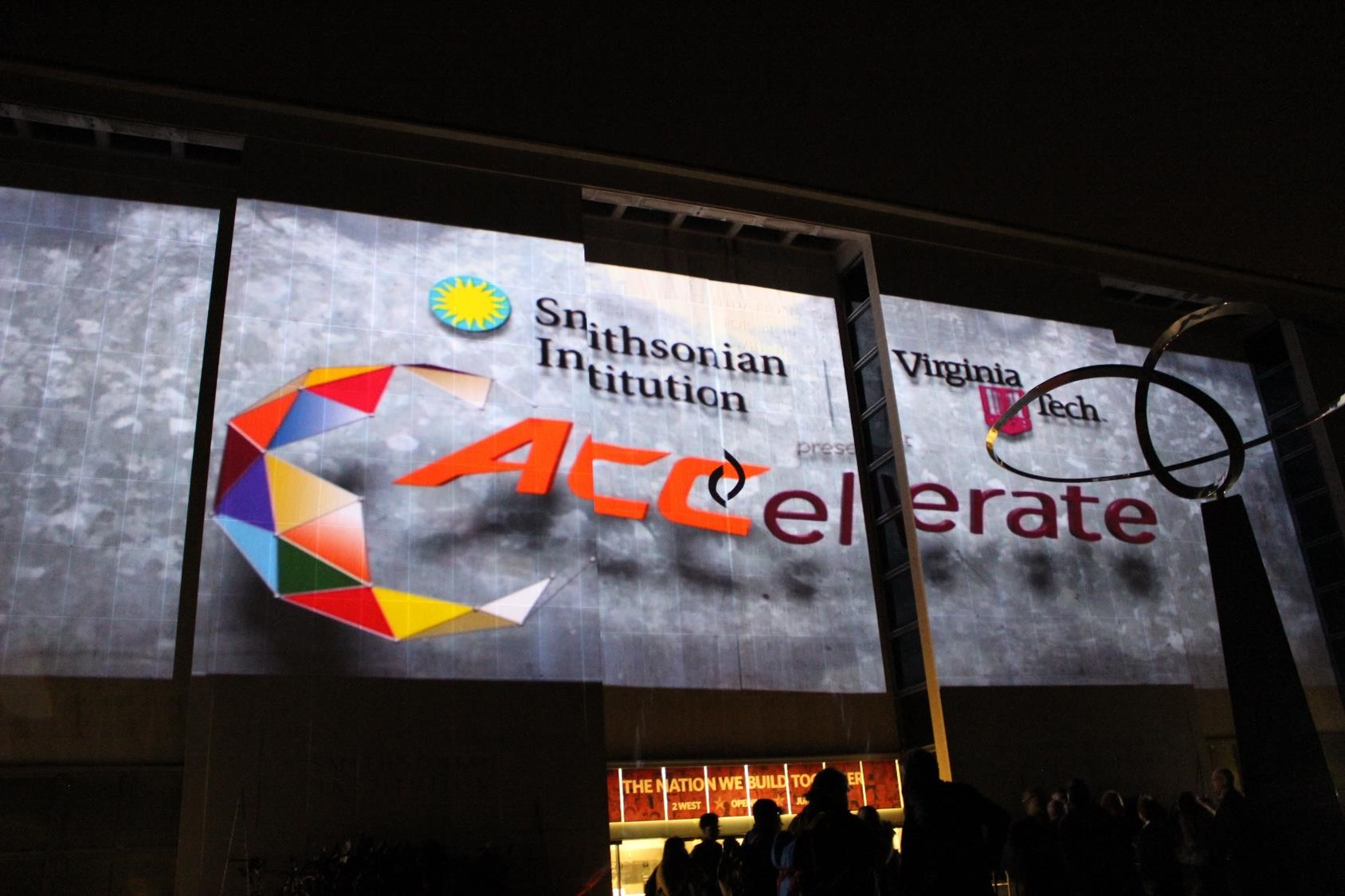 A projection of the ACCelerate logo is displayed on the exterior of the Smithsonian National Museum of American History.