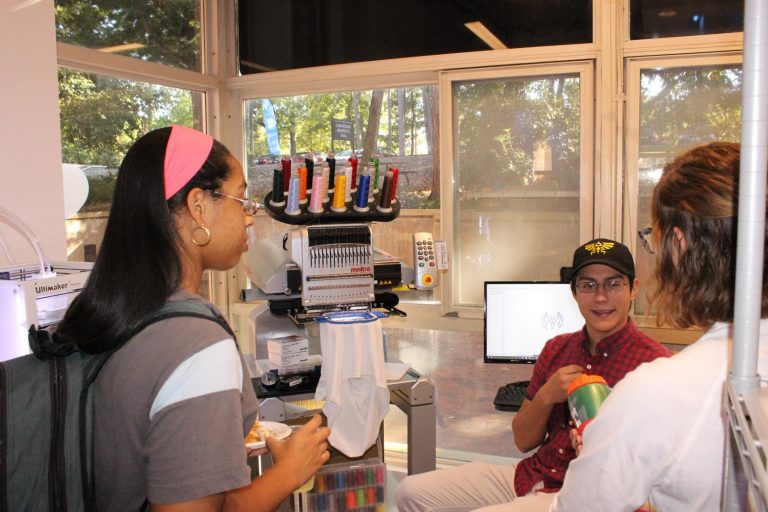 Two students talk with first-year stududent Gustavo Rios about how to use the embroidery machine.