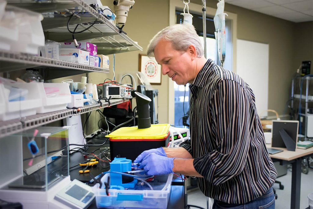 Tony Voiers uses blue dye and  a substance that mimics human tissue to test the transfer of the blue dye through the tissue substance